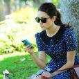 Absorbée par son iPhone, Emmy Rossum passe du bon temps dans un parc de Los Angeles. Le 15 août 2012