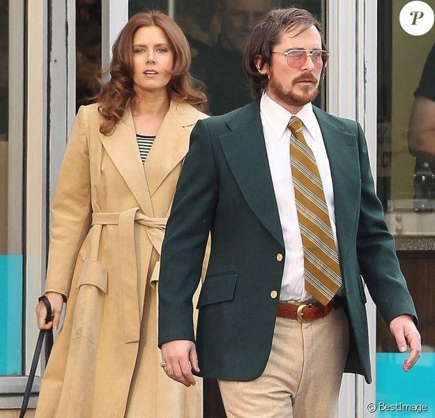 Une ravissante Amy Adams derrière le méconnaissable Christian Bale sur le tournage du prochain long-métrage de David O. Russell près de Boston, Massachusetts, le 21 mars 2013.