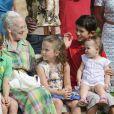 La princesse Athena sur les genoux de son cousin Nikolai. La famille royale de Danemark en séance photo le 26 juillet 2013 pour les médias dans le parc du château de Grasten, résidence d'été royale. Autour de la reine Margrethe II et du prince Henrik, le prince Frederik et la princesse Mary, et le prince Joachim et la princesse Marie, avec tous leurs enfants, ainsi que la princesse Benedikte, le prince Gustav et la princesse Alexandra de Sayn-Wittgenstein-Berleburg, et la reine Anne-Marie de Grèce étaient rassemblés.