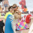 Denise   Richards   a déposé    à la plage   ses   filles   Lola   et   Sam, qui   avaient un cours de surf,      et   les jumeaux  de Brooke Mueller et Charlie Sheen, Bob et Max . Le 31 juillet 2013 à Malibu.   L'  ancien mannequin était   habillé d'  une robe   bustier   crème   et  portait des  sandales à lanières  .