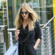 Rosie Huntington-Whiteley sort de chez Mark & Spencer à Londres, habillée de lunettes Miu Miu, d'une combi-pantalon en soie Gerard Darel et de sandales Michael Kors. Le 21 août 2013.