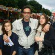 Anthony Delon et ses filles Loup et Liv lors de l'inauguration de la fête foraine des Tuileries à Paris le 28 juin 2013