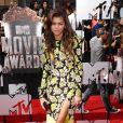 Zendaya assiste aux MTV Movie Awards 2014 au Nokia Theatre L.A. Live, habillée d'une robe à motifs floraux fendue Emanuel Ungaro (collection automne-hiver 2014), d'une pochette Swarovski et de souliers Christian Louboutin. Los Angeles, le 13 avril 2014.