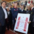 Le prince Albert de Monaco présente un maillot hommage à Michael Schumacher lors du World Stars Football Match entre la Star Team Monte Carlo et la F1 Driver Team, au stade Louis II de Monaco, le 20 mai 2014
