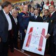 Le prince Albert de Monaco présente un maillot en hommage à Michael Schumacher lors du World Stars Football Match entre la Star Team Monte Carlo et la F1 Driver Team, au stade Louis II de Monaco, le 20 mai 2014