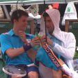Novak Djokovic profite d'une averse pour partager un verre et échanger avec un jeune ramasseur de balles, le 26 mai 2014 à Roland-Garros