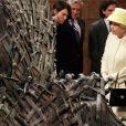 """Elizabeth II devant le fameux Trône de Fer et les stars de la série """"Game of Thrones"""". Visite des décors de la série aux Titanic Studios à Belfast, le 24 juin 2014."""