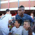 Paul Pogba avec des enfants avant l'entraînement de l'équipe de France à Ribeirao Preto au Brésil le 17 juin 2014