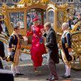 Le roi Willem-Alexander aide son épouse la reine Maxima des Pays-Bas, en robe Valentino, lors de leur arrivée au Parlement à La Haye pour le Prinsjesdag, la cérémonie d'ouverture de l'année parlementaire, le 16 septembre 2014