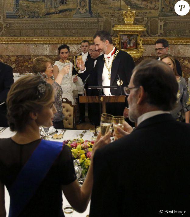 Letizia d'Espagne, de dos, trinque avec le chef du gouvernement Mariano Rajoy tandis que Felipe en fait autant avec Michelle Bachelet, le 29 octobre 2014 au palais du Pardo, à Madrid.