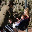 Michelle Hunziker, son mari Tomaso Trussardi et leur fille Sole font de la balançoire dans un parc à Milan, le 8 novembre 2014.