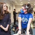 Kate Middleton, enceinte, a tenté de communiquer avec la jeune golfeuse Emma Allen en plein test d'effort alors qu'elle visitait le 12 novembre 2014 le   GSK Human Performance Lab à Brentford (ouest de Londres) dans le cadre de son patronage de SportsAid.