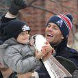Tom Brady et son fils Benjamin (5 ans) fêtent la victoire de son équipe les New England Patriots au Super Bowl lors d'une parade à Boston, le 4 février 2015 en brandissant le trophée pendant que la foule applaudit l'équipe.