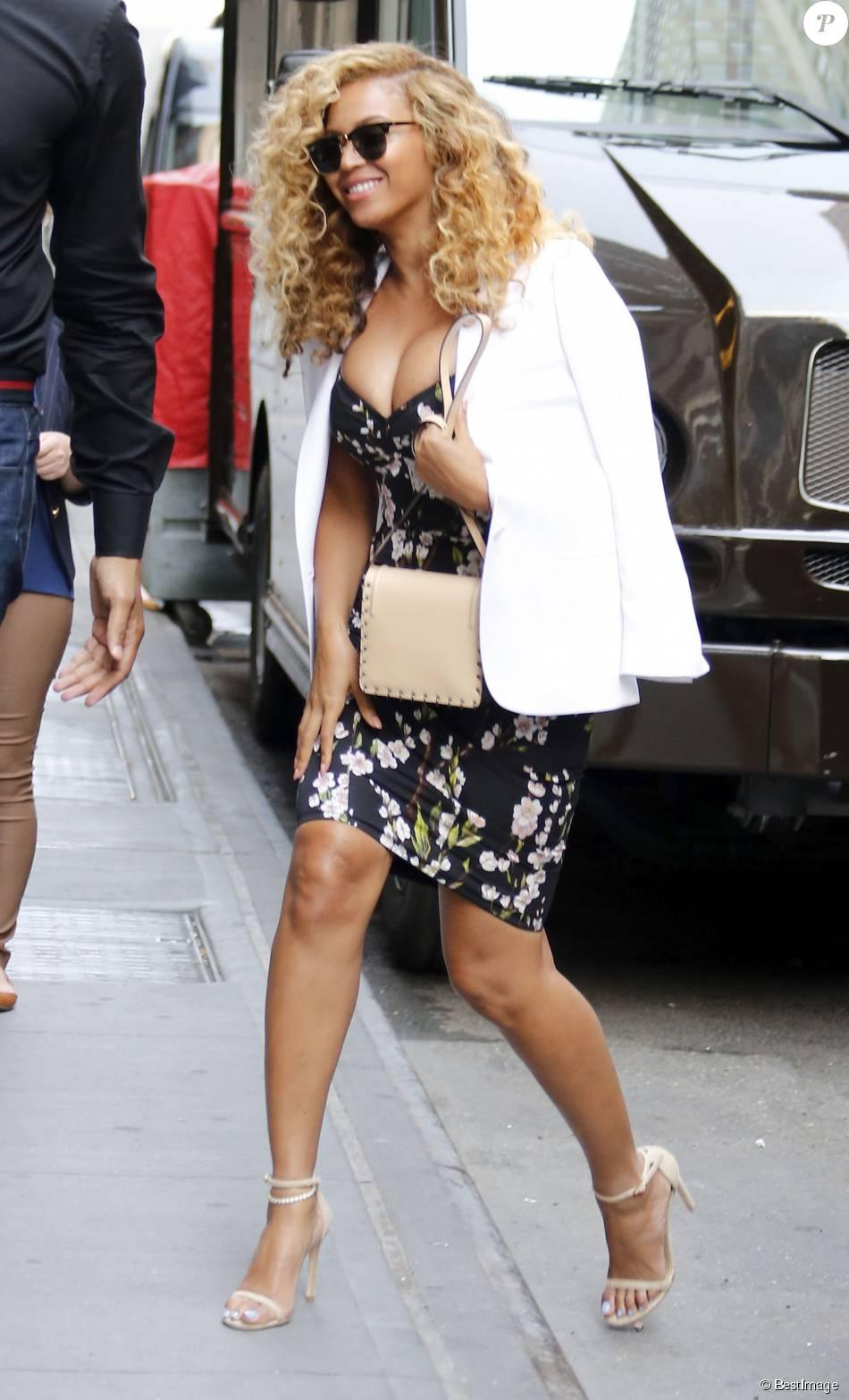 Beyoncé Knowles se rend au siège de Parkwood Entertainment à New York, habillée d'un blazer blanc porté à l'italienne, d'une robe noire imprimée de fleurs de cerisier Dolce & Gabbana et de sandales Stuart Weitzman (modèle Nudist). Des lunettes Ray-Ban (collection Clubmaster) et un sac beige Dannijo complètent sa tenue. Le 27 juillet 2015.