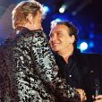 Michel Sardou et Johnny Hallyday sur scène lors d'un concert au Parc de Sceaux, le 16 juin 2000.