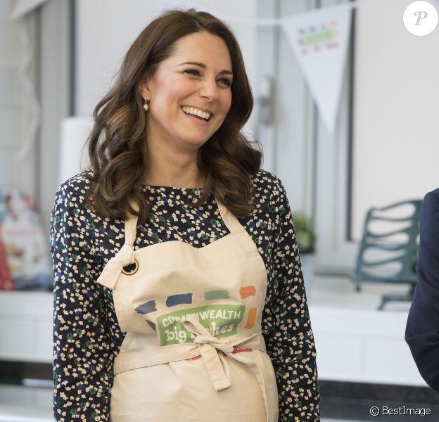 La duchesse Catherine de Cambridge, enceinte, et le prince William ont pris part aux préparatifs du Commonwealth Big Lunch le 22 mars 2018 au centre communautaire St Luke à Londres. Son ultime engagement avant son congé maternité, Kate l'aura accompli... en tablier !