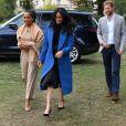 Meghan Markle, duchesse de Sussex, portant une jupe Misha Nonoo et accompagnée par sa mère Doria Ragland et son mari le prince Harry, lors de la réception au palais de Kensington le 20 septembre 2018 des femmes d'une cuisine communautaire qu'elle avait rencontrées auparavant.