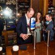 Kate Middleton a servi une bière à son mari le prince William lors d'une réception à l'Empire Music Hall à Belfast, le 27 février 2019.