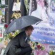 Le prince Harry, le 30 août 2017, déposant de fleurs et observant les témoignages d'affection du public à la mémoire de Lady Di sur les grilles du palais de Kensington, à la veille du 20e anniversaire de sa mort.