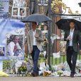 Le prince William et le prince Harry, le 30 août 2017, observant les témoignages d'affection du public à la mémoire de Lady Di sur les grilles du palais de Kensington, à la veille du 20e anniversaire de sa mort.