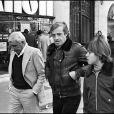 Archives - Jean-Paul Belmondo avec son fils Paul et Charles Gérard sur les Champs-Elysées de Paris. Le 4 février 1977.