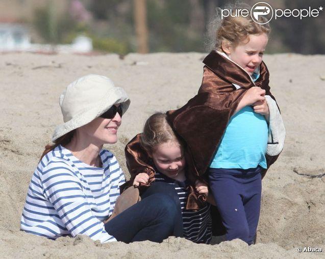 Marcia Cross et ses jumelles Eden s'amusent sur la plage en creusant un trou dans le sable ! Enveloppées dans leur serviette de plage, les jumelles passent du bon temps avec leur mère à Santa Monica, Los Angeles, le 22 avril 2011.
