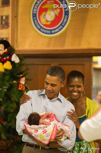 Barack et Michelle Obama visitant une base de la marine nationale le 25 décembre 2011 à Hawaï : en portant un bébé de militaire, le couple offre une photo superbe
