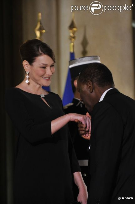 Carla Bruni-Sarkozy et Nicolas Sarkozy posent devant le seuil du palais présidentiel de l'Elysée avec Alassane  Ouattara, président ivoirien, et son épouse Dominique Ouattara, le 26 janvier 2012, à l'occasion d'un dîner d'Etat