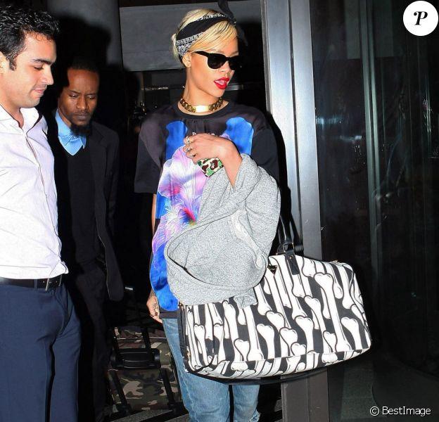 Rihanna quitte son hôtel pour se rendre à l'aéroport JFK de New York. La chanteuse porte un t-shirt Givenchy sur un jean assez large, des bottes noires Alexander Wang et un sac Joyrich. Le 18 mars 2012.