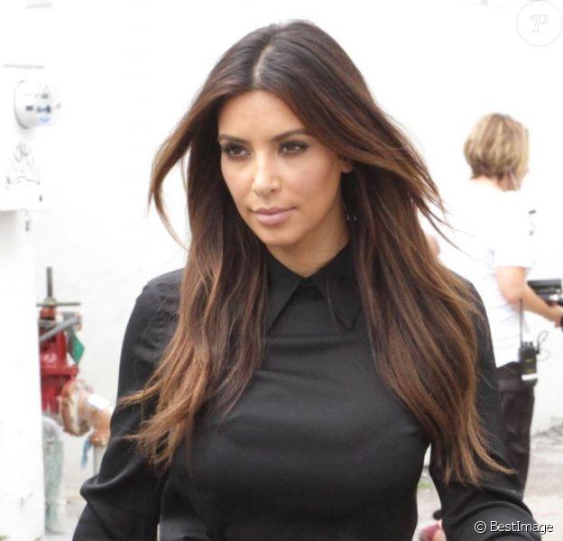 Kim Kardashian, sexy en chemise noire, jupe en cuir et sandales Tom Ford. Miami, le 16 septembre 2012.