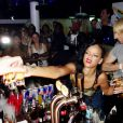 """Après son concert, Rihanna passe derrière le bar pour ses fans, à Stockholm lors de son """"777 Tour"""", le 16 novembre 2012."""