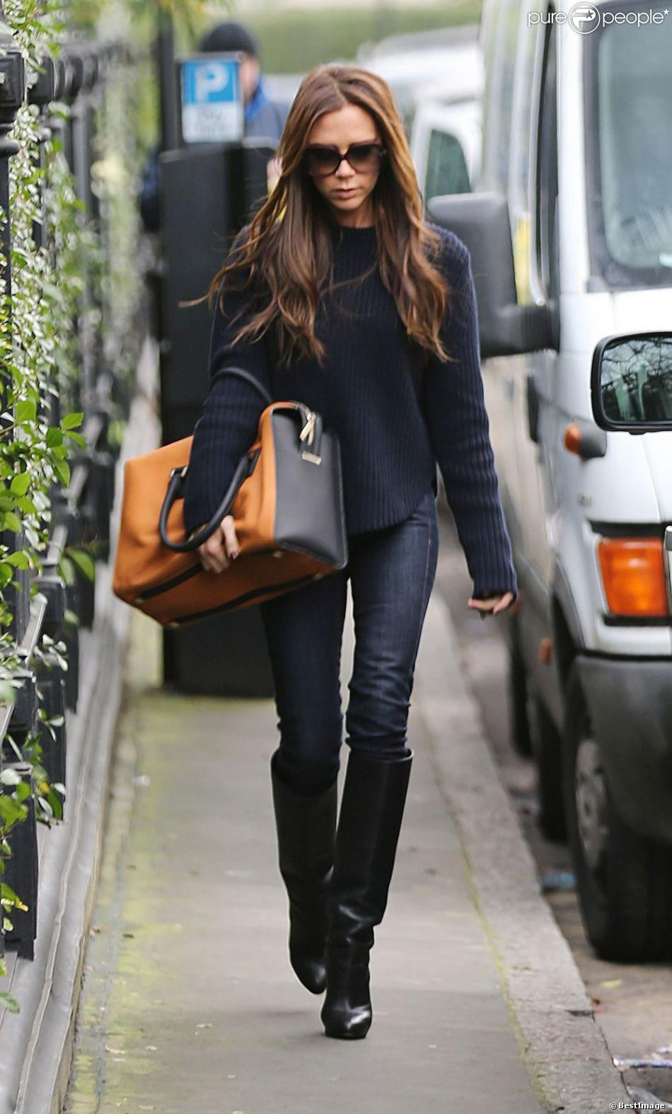 Victoria Beckham porte un sweater et un jean bleu foncé avec un sac Victoria Beckham et des bottes Christian Louboutin. Londres, le 28 janvier 2013.
