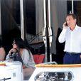 Eric Besson, au téléphone, et sa femme Yasmine se promenant sur la Croisette en plein Festival de Cannes le 23 mai 2013. Ils font escale sur un yacht luxueux