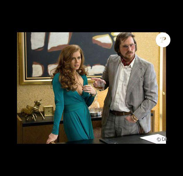 Amy Adams, vintage et décolletée devant Christian Bale dans American Hustle.
