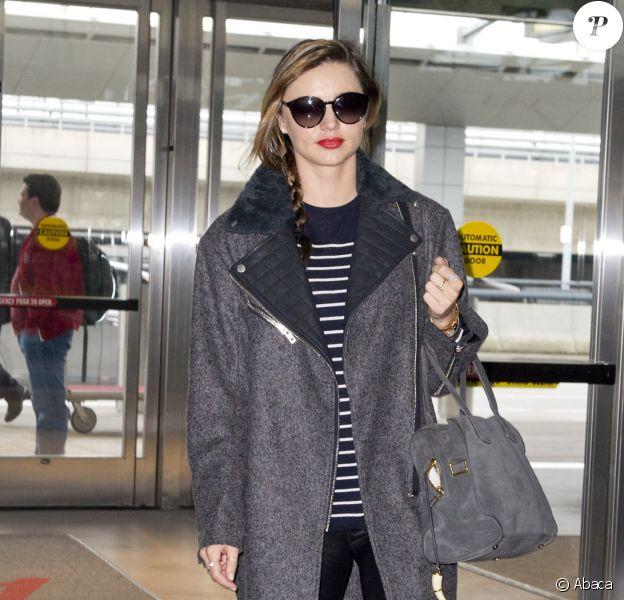 """Miranda Kerr surprise à l'aéroport JFK à New York, porte le manteau """"Turner"""" de Rag & Bone, un sweater rayé, un pantalon en cuir, un sac """"Pierre"""" de Balmain par Aurélie Bidermann et des bottines Isabel Marant. Le 7 novembre 2013."""