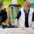 La princesse Margriet des Pays-Bas aide à vernir du mobilier à Zeewolde, sur un site de l'Institut pour l'Education environnementale et le développement durable, le 21 mars 2014 pour la 10e Journée du bénévolat organisée par le Fonds Orange.