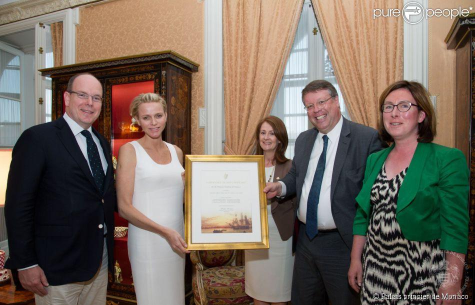 """La princesse Charlene de Monaco reçoit en présence de son mari le prince Albert II un """"Certificate of Irish Heritage"""" attestant de ses racines irlandaises, des mains de Son Excellence l'Ambassadeur d'Irlande en France, Rory Montgomery, le 29 juillet 2014 au palais princier de Monaco. En présence également de Finola O'Mahony de Tourism Ireland et Fiona Fitzsimons de l'agence de généalogie Eneclann."""