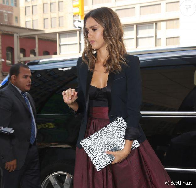 Jessica Alba rentre à l'hôtel Trump Soho à New York, habillée d'un blazer The Kooples, d'une jupe taille haute et plissée Katharine Kidd (modèle Blackthorne), d'une pochette Saint Laurent et de sandales Giuseppe Zanotti. Le 13 août 2014.
