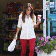 Exclusif - Eva Longoria de sortie à Hollywood, porte des lunettes de soleil Ray-Ban, une chemise blanche, un jean rouge J Brand et des sandales Jimmy Choo (modèle Lance). Le 13 août 2014.