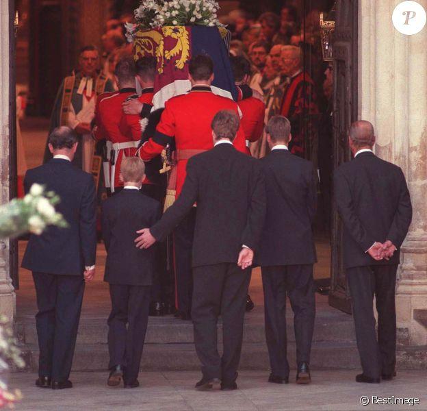 """Charles Spencer passant une main réconfortante dans le dos du prince Harry à l'entrée de l'abbaye de Westminster... Le prince William et le prince Harry, alors âgés de 15 et 12 ans, ont dû marcher derrière le cercueil de leur mère la Lady Diana en public avec le duc d'Edimbourg, le prince Charles et le comte Charles Spencer, pendant une interminable demi-heure lors des obsèques nationales de la princesse le 6 septembre 1997 à Londres. """"Bien sûr qu'ils ne voulaient pas faire ça"""", a révélé en juillet 2017 leur oncle Charles Spencer."""