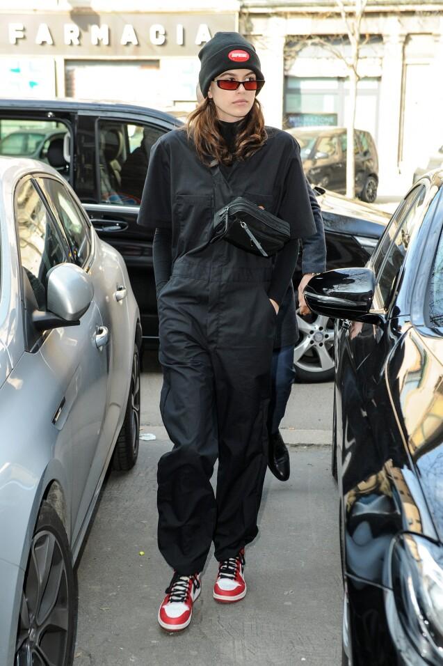 Kaia Gerber porte un bonnet Supreme, une combinaison Dickies, une sacoche  Prada et des
