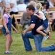 Peter Phillips prend sa fille Isla sur son dos devant sa grande soeur Savannah lors du Festival of British Eventing à Gatcombe Park le 2 août 2019.