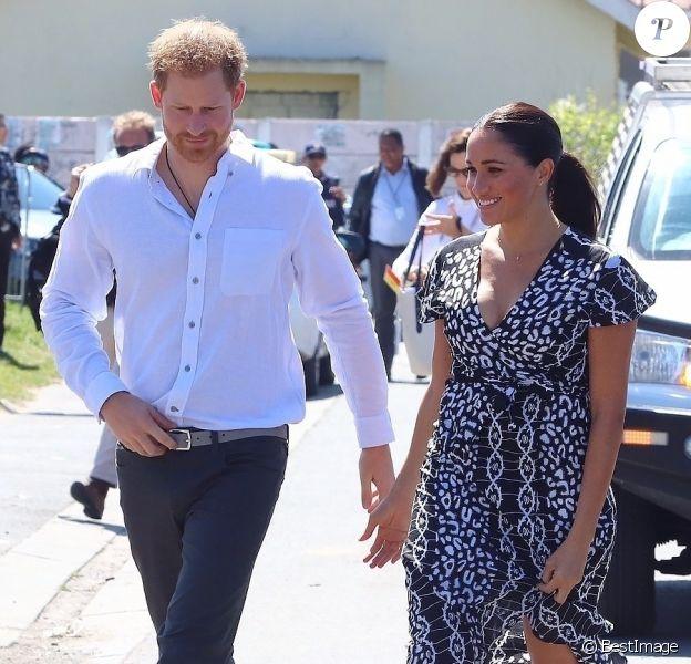 Le prince Harry, duc de Sussex, et Meghan Markle, duchesse de Sussex, arrivent main dans la main en visite dans le township de Nyanga en Afrique du Sud le 23 septembre 2019.