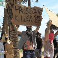 """Machine Gun Kelly proteste contre les violences policières, suite à la mort de George Floyd, avec un carton affichant le message """"Poursuivez les policiers tueurs"""". Los Angeles, le 31 mai 2020."""