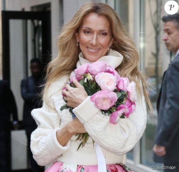 Celine Dion rayonnante et très souriante dans un ensemble pull écru et jupe bouffante fleurie salue ses fans à la sortie de son hôtel à New York, le 8 mars 2020