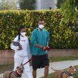 """Jesse Williams (""""Grey's Anatomy"""") et sa compagne Taylour Paige, équipés de masques de protection, promènent leurs chiens pendant l'épidémie de coronavirus (Covid-19) à Los Angeles, le 16 avril 2020."""