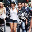 Miley Cyrus rayonnante et surtout très branchée, vêtue d'un micro short en jean porté avec un top blanc et un long gilet Goddis Linsey, ainsi qu'avec un petit canotier sur la tête, et des bottines à bouts ouverts et à lacets tellement tendance.