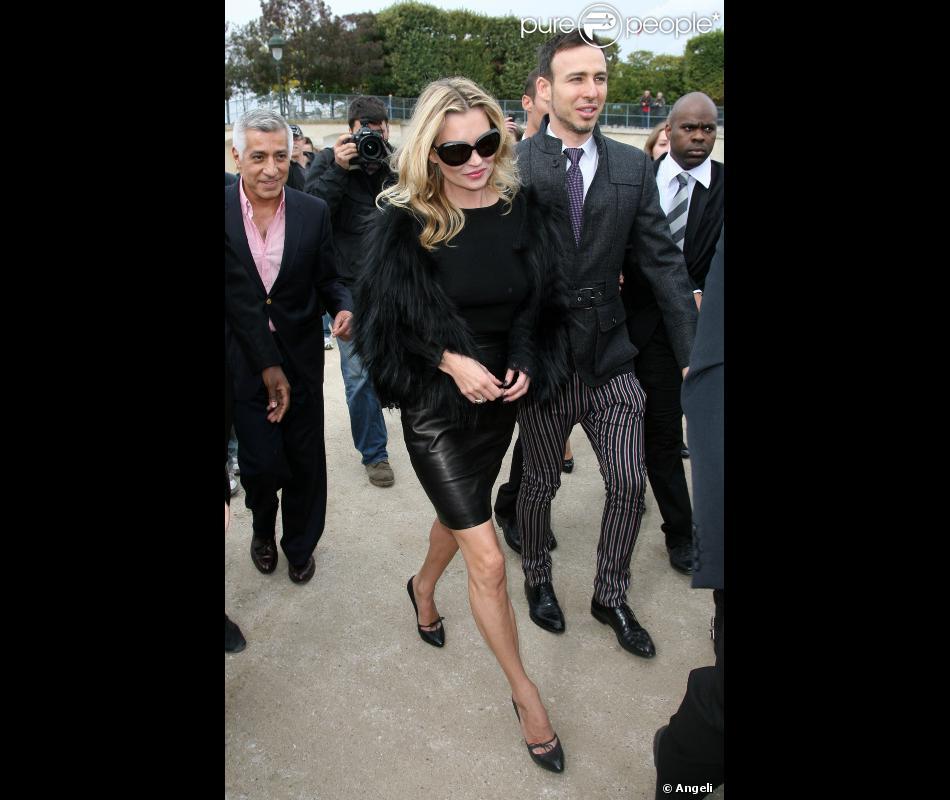 Kate Moss en total look black pour le défilé Dior. Jupe en cuir droite,  escarpins pointus, lunettes XXL, le look de star hollywoodienne est assuré. 66aa6d2b0402