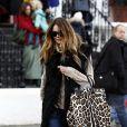 """Cheveux """"wild"""", blouson en poils, Elle McPherson """"chic-ise"""" sa tenue avec son sac léopard."""