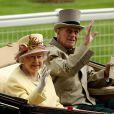 Ascot 2011, jour 4, vendredi 17 juin 2011 : après le rose bonbon de la veille, place au jaune lumineux pour la reine Elizabeth II. La pluie persistante oblige les bibis à se planquer sous les parapluies, mais le rendez-vous tient ses promesses.